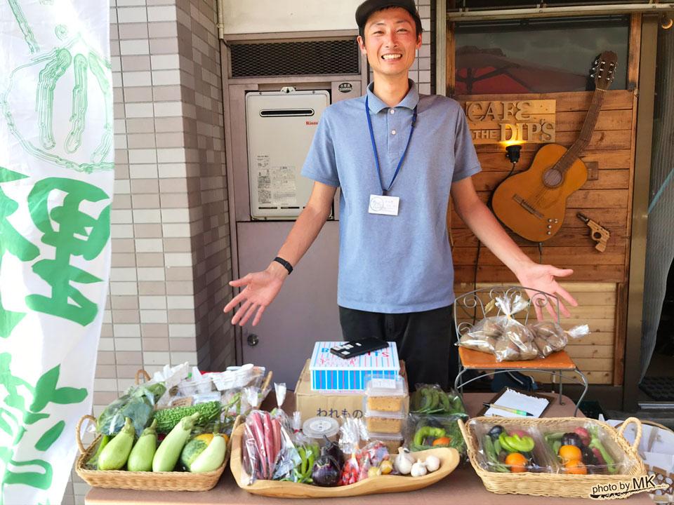 自然農法の野菜を前にしている尾崎将太さん